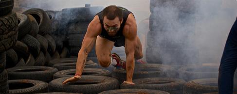 A man crawling through tires