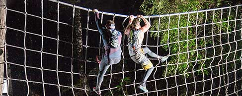 Photo of two people climbing over a net